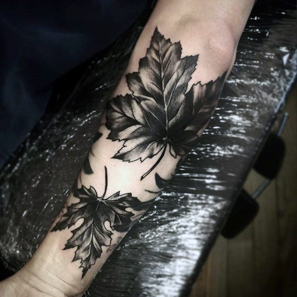 Two blackwork maple leaf tattoos