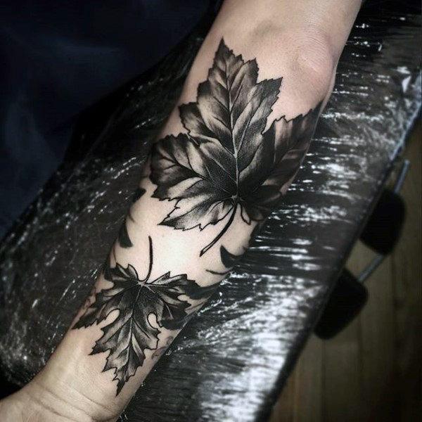 Two blackwork maple leaf tattoos