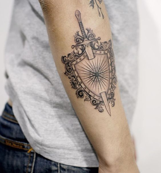 Sword and shield tattoo on the forearm