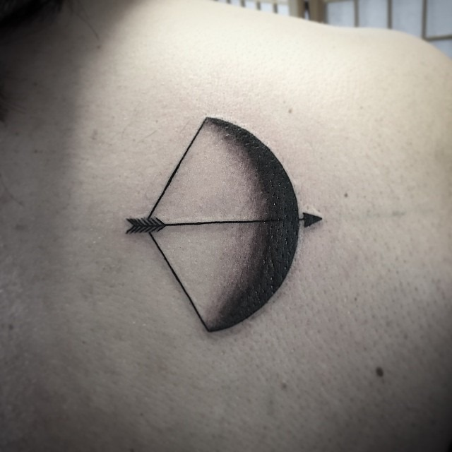 Tattoo of a crescent moon as a bow and an arrow on the right shoulder blade
