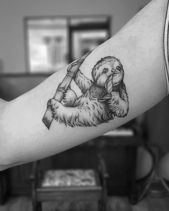 Tattoo of a sloth eating a bamboo leaf